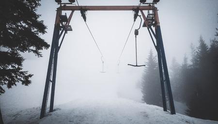 Empty t-bar lift in fog in Karpaty mountains