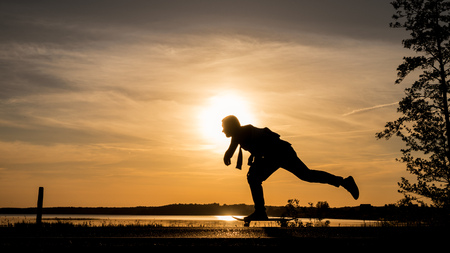 Skater on road make wide pushing against the sunset