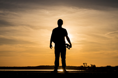 Skater standing on road and holding a skateboard against the sunset
