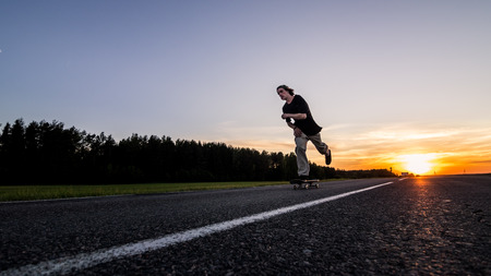Skater make pushing on empty road at the beautiful sunset