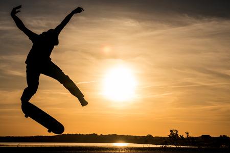 Skater jump against the beautiful orange sunset