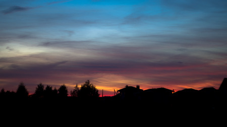Silhouette of houses in village on beautiful red sunset Banco de Imagens