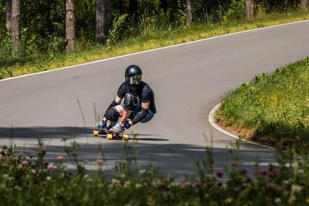 Longboard downhill rider make fast in a turn