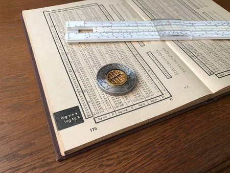 Book of Logarithmic Tables, Slide Rule and a Silver Coin with Abacus