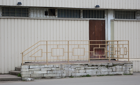 Entrance to the building, concrete porch with metal railings