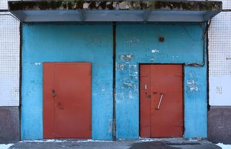 Metalowe brązowe drzwi w niebieskiej ścianie