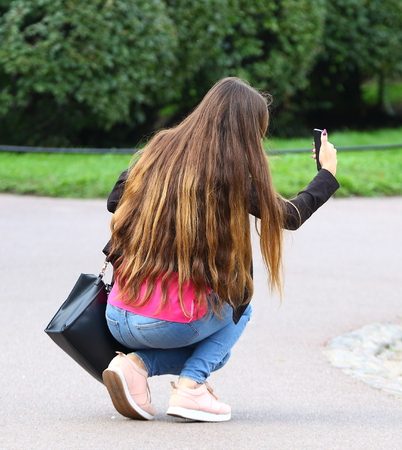 The girl with long hair taking a selfie squatting