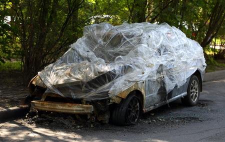 Burnt car covered with polyethylene Reklamní fotografie