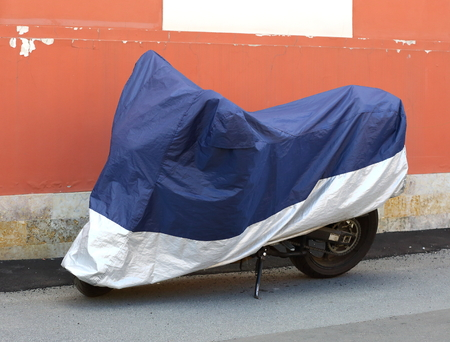 Motorcycle covered with a cover Фото со стока