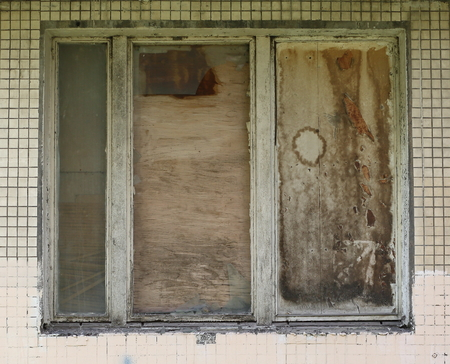 Old window with wooden frame boarded up with plywood