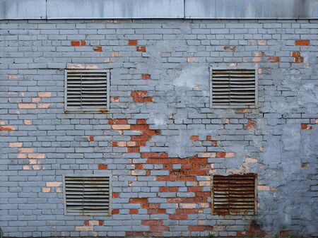 Shabby old painted brick wall with vents