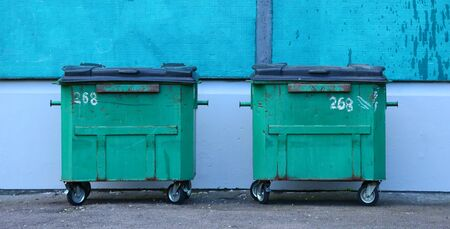 Green plastic dumpsters on wheels against the wall of the house 版權商用圖片
