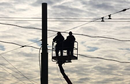 Installers Working on high-altitude workers with cables at height on a background cloudy sky