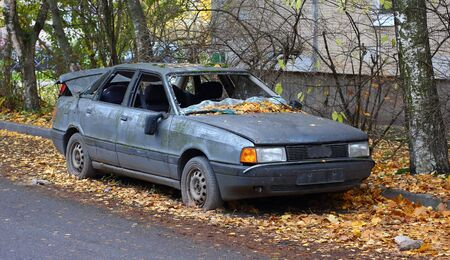 Old broken abandoned dark gray car on yellow leaves in the yard of an apartment building
