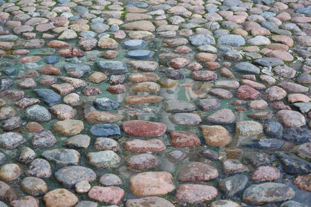 The pavement of different cobblestones filled with water Reklamní fotografie