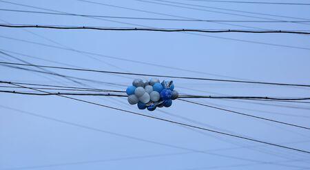Veelkleurige stuiterballen vast in de elektrische draden in de lucht Stockfoto