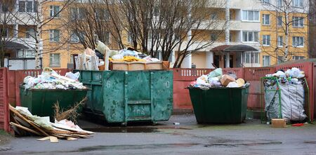 Overflowing with household waste bins in the yard of a residential building Stok Fotoğraf