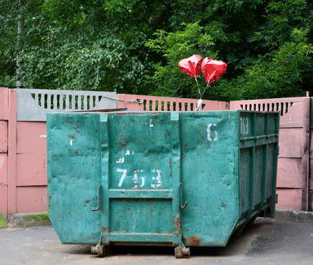 Two a red heart shaped balloons above a green dumpster