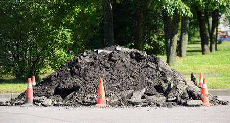A pile of dirt on the road surrounded by red cones Banco de Imagens - 153285256