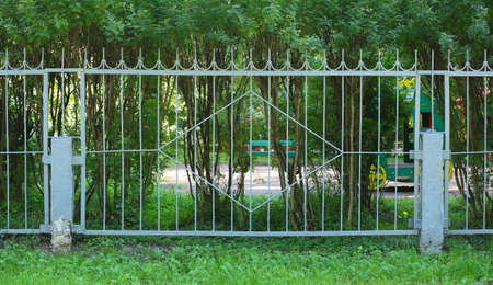 Metal lattice fence of the green garden Banco de Imagens