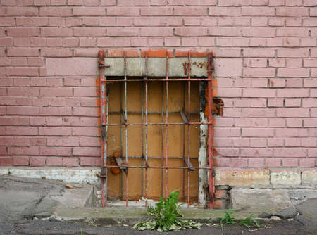 A basement window with a metal barrier Banco de Imagens - 152924282