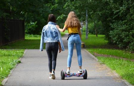 A girl teaches her friend to ride a gyro scooter, prospekt Bolshevikov, Saint Petersburg, Russia August 2020 Editorial