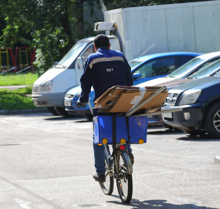 Waste paper collector in a blue uniform on a Bicycle, prospekt Bolshevikov, Saint Petersburg, Russia August 2020