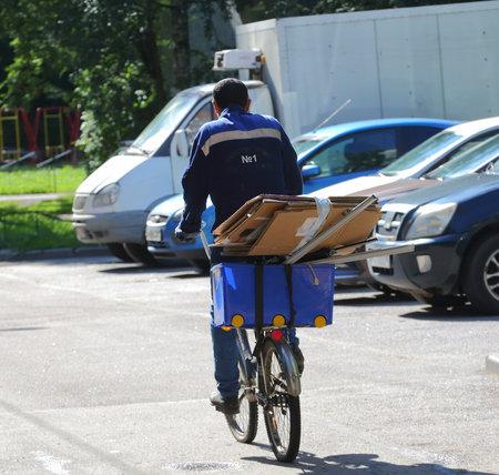 Waste paper collector in a blue uniform on a Bicycle, prospekt Bolshevikov, Saint Petersburg, Russia August 2020 Banco de Imagens - 152968141