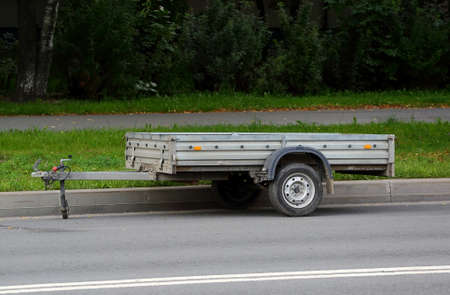 An open automobile trailer is parked on the road near a green lawn Banco de Imagens - 153180308