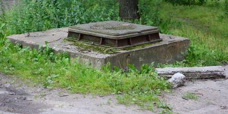 An old concrete manhole with a metal cover in the green grass Banco de Imagens - 153438486