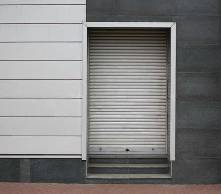 Closed metal roller shutter entrance to the modern building