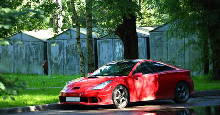 A red sports car is parked in the courtyard by the garages Banco de Imagens - 153304195