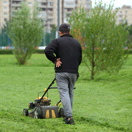A Park employee mows the grass with a lawn mower, Rossiyskiy prospect, Saint Petersburg, Russia, August 2020