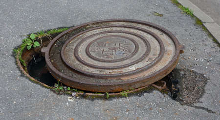 The rusty lid of an old sewer manhole has been pushed to the side Banco de Imagens - 153383198
