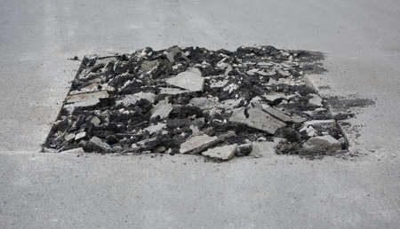 A square section of broken road surface to replace. Banco de Imagens - 153478761