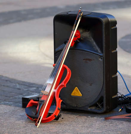The electric violin is leaning against the sound column Banco de Imagens - 153581423