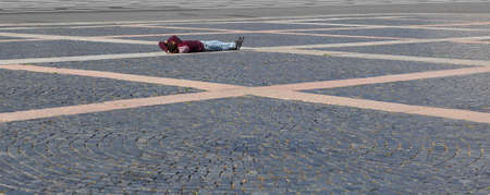 A man lies on the cobblestones of the city square, Palace square, Saint Petersburg, Russia, August 2020 Editorial