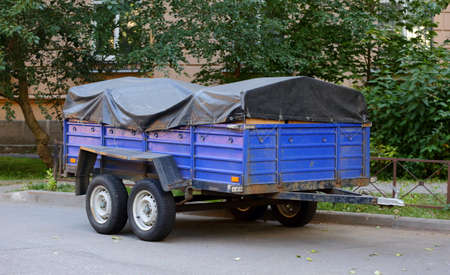 A heavy four-wheeled cargo trailer with a dark awning is parked near the green trees Banco de Imagens - 153909994