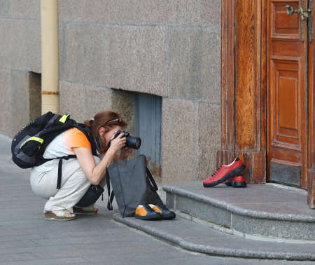 A woman photographer photographs shoes on the stone steps of the old porch, Dvortsovaya embankment, Saint Petersburg, Russia, August 2020 Banco de Imagens - 154179171