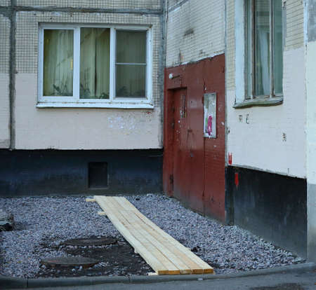 Wooden bridges for the entrance to the house when repairing the road surface, Bolshevikov prospekt 5, Saint Petersburg, Russia, August 2020