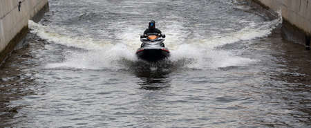 A man on a jet ski rides on a canal, Griboyedov canal, Saint Petersburg, Russia, August 2020 Banco de Imagens - 154329049