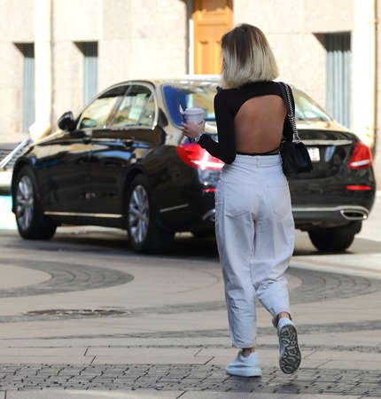 A fashionable woman in white trousers and with a bare back walks along the cobblestones to the car, Bolshaya Morskaya ulitsa, Saint Petersburg, Russia, September 2020