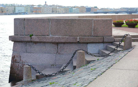 Granite steps of descent to the water with cast-iron chains, Universitetskaya embankment, Saint Petersburg, Russia, September 2020 Banco de Imagens - 154600401