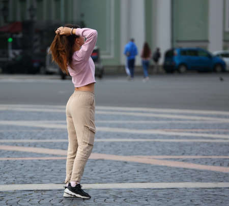 A girl in a pink jacket and beige trousers on the cobblestone city square, Palace square, Saint Petersburg, Russia, September 2020