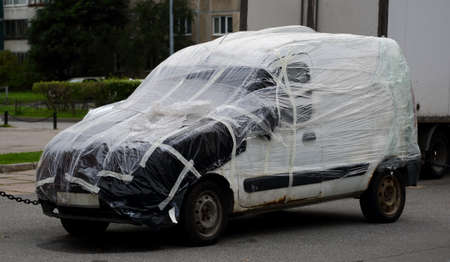 An old broken down car is wrapped in plastic wrap