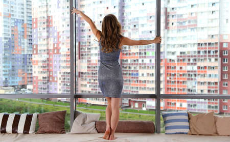Girl in a shiny dress at the panoramic window