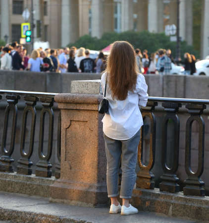 A buxom-haired girl in a white shirt stands at a cast-iron fence with granite pillars