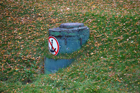 A manhole with a forbidding sign on the Bank in green grass and yellow leaves