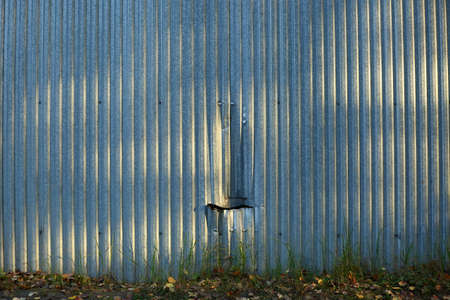 Corrugated metal fence with a dent and a ragged hole Banco de Imagens