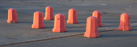 A group of orange concrete traffic stops in the Parking lot Banco de Imagens